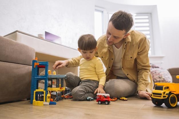 Pai e filho brincando com caminhões e peças de lego Foto gratuita