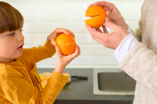 Pai e filho brincando com laranjas Foto gratuita