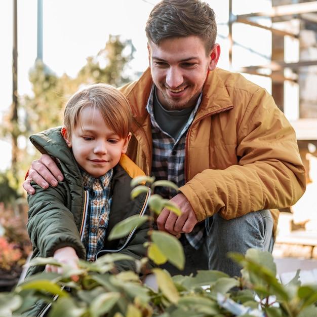 Pai e filho colhendo uma planta juntos Foto gratuita