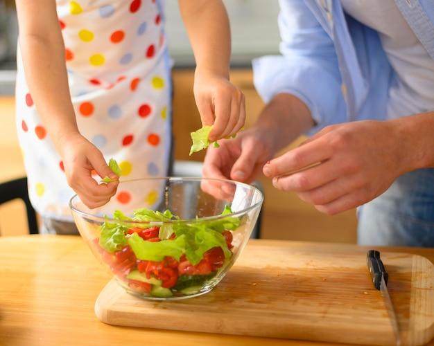 Pai e filho comendo uma salada Foto gratuita