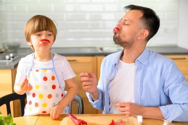 Pai e filho comendo vegetais saudáveis Foto Premium