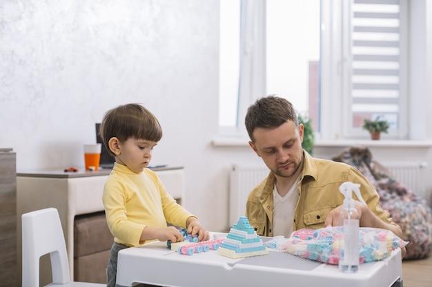 Pai e filho construindo brinquedos de peças de lego dentro de casa Foto gratuita