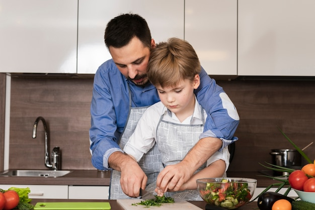 Pai e filho cortar legumes Foto gratuita