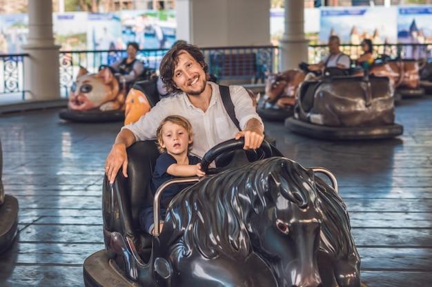 Pai e filho dando um passeio no carro de choque no parque de diversões. Foto Premium