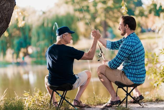 Pai e filho dão cinco um ao outro na natureza. Foto Premium
