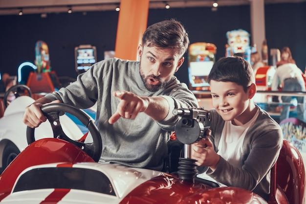 Pai e filho de joyfull que sentam-se no carro do brinquedo na alameda. Foto Premium