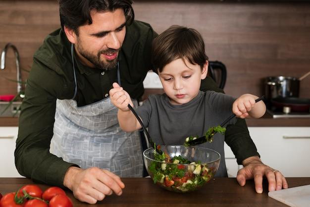 Pai e filho em casa fazendo salada Foto gratuita