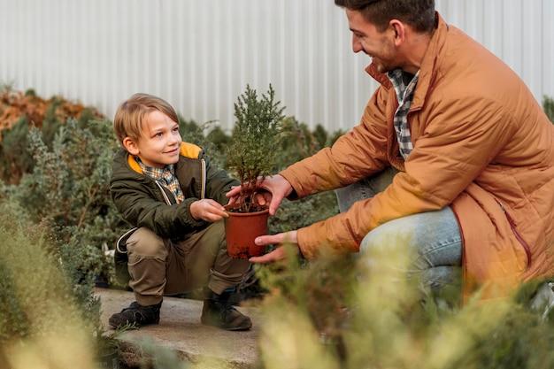 Pai e filho em um viveiro de árvores juntos Foto gratuita