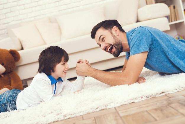 Pai e filho está jogando no braço de wrestling. Foto Premium