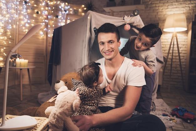 Pai e filho estão brincando com irmãzinha à noite. Foto Premium
