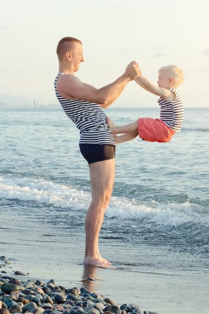 Pai e filho estão brincando na praia. passatempo divertido Foto Premium