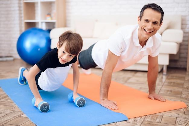 Pai e filho estão envolvidos em fitness em conjunto com fitball. Foto Premium