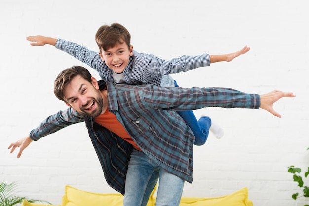 Pai e filho imitando aviões Foto gratuita