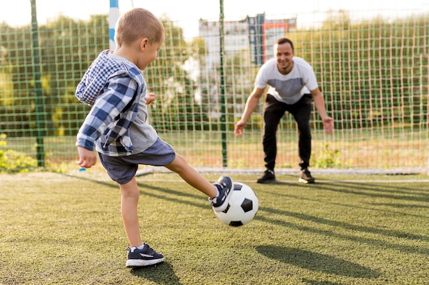 Pai e filho jogando futebol Foto gratuita