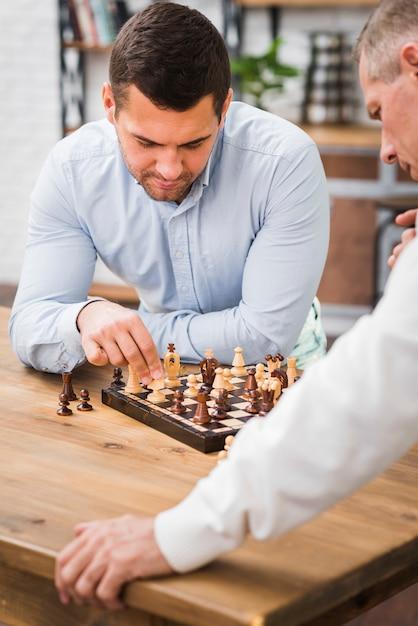 Pai e filho jogando xadrez na mesa Foto gratuita