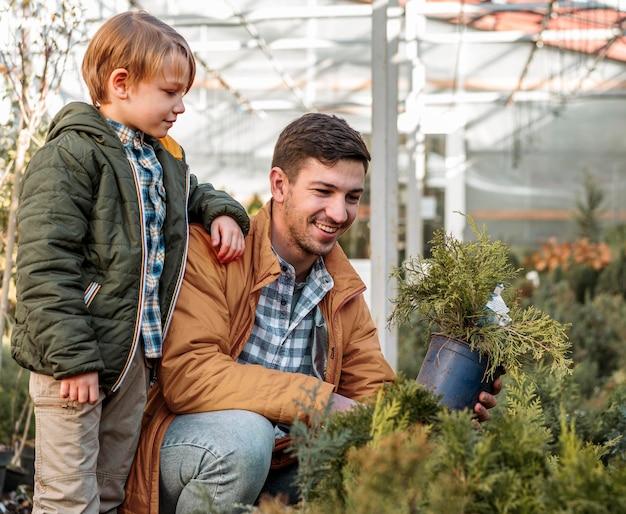 Pai e filho juntos comprando uma árvore Foto gratuita