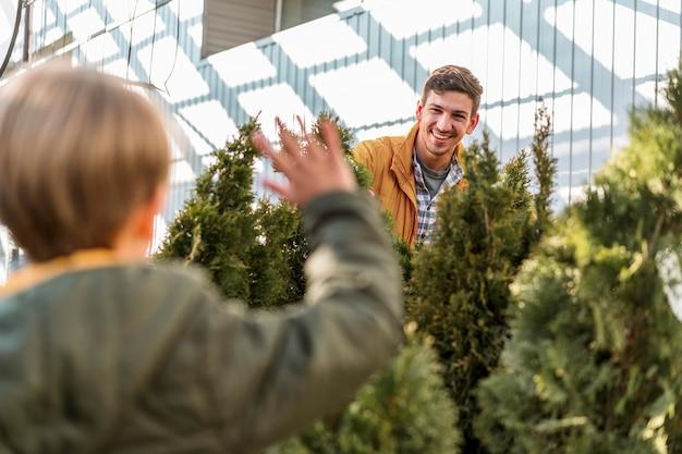Pai e filho juntos em um viveiro de árvores, colhendo plantas Foto gratuita