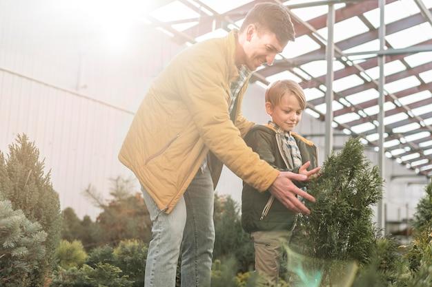 Pai e filho juntos em um viveiro de árvores olhando para a vegetação Foto gratuita