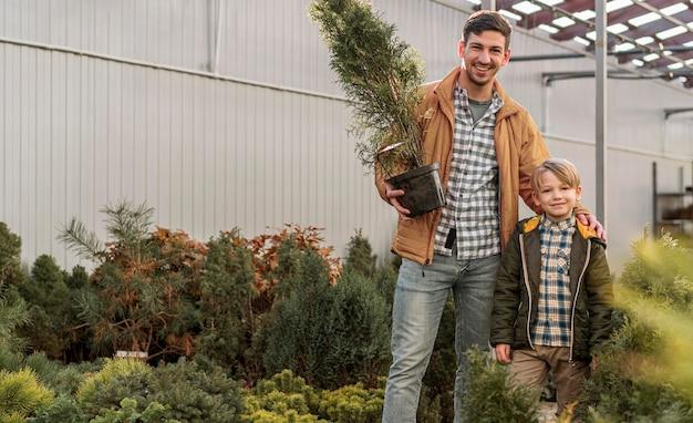 Pai e filho juntos em um viveiro de árvores posando com maconha Foto gratuita