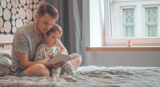 Pai e filho leram um livro juntos, sorrindo e se abraçando Foto Premium