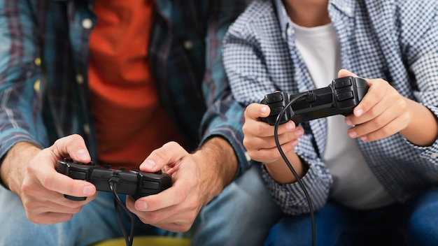 Pai e filho mãos jogando no console Foto gratuita
