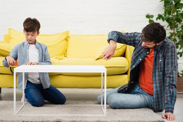 Pai e filho medindo uma mesa Foto gratuita