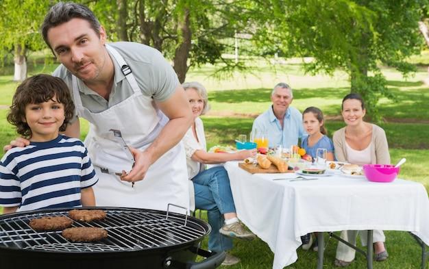 Pai e filho na churrasqueira com a família almoçando no parque Foto Premium