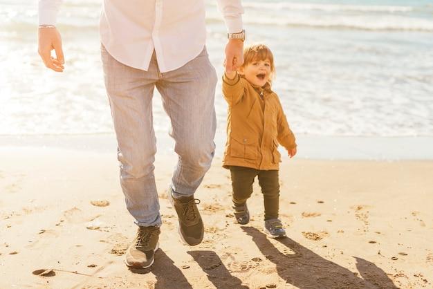 Pai e filho na costa iluminada pelo sol Foto gratuita