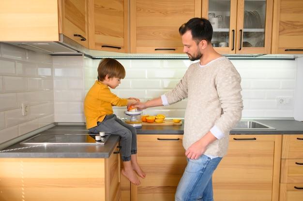 Pai e filho na cozinha fazendo um suco Foto gratuita