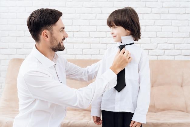 Pai e filho na mesma roupa. papai ajuda o filho. Foto Premium