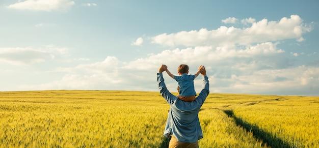 Pai e filho no campo de trigo, criança sentada nos ombros do pai Foto Premium