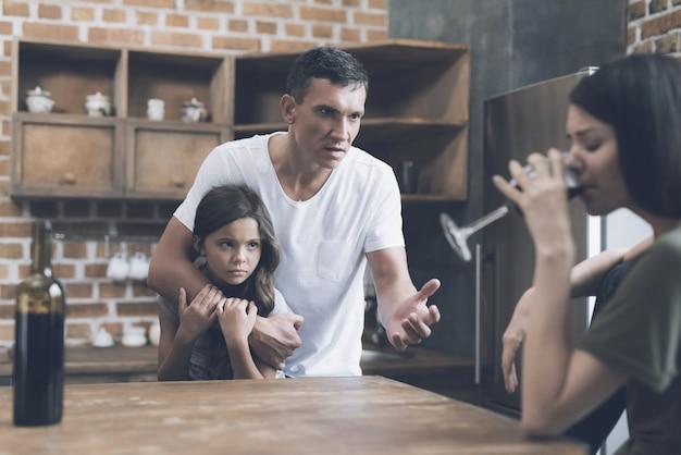 Pai e filho olhar para mãe bêbada na cozinha Foto Premium