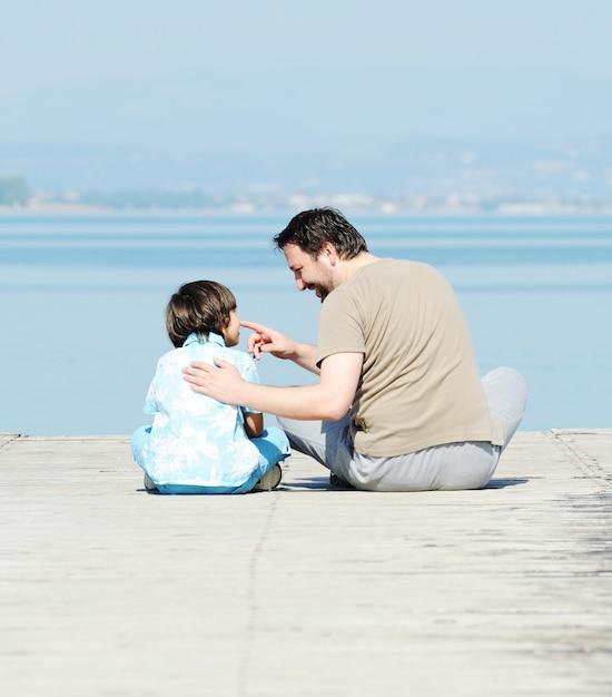 Pai e filho pela doca em um lindo lago Foto Premium