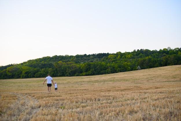 Pai e filho pequeno estão andando por um campo de trigo segado. Foto Premium