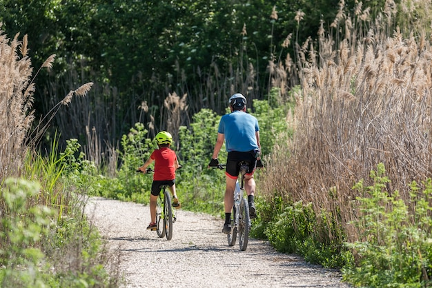 Pai e filho praticando esporte de bicicleta Foto Premium