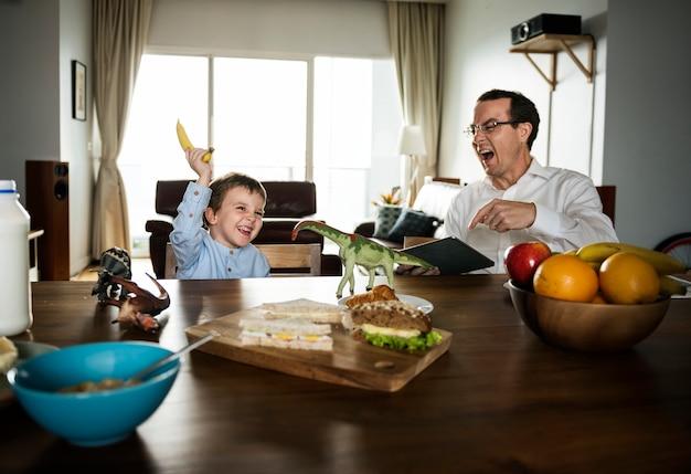 Pai e filho se divertindo na mesa de café da manhã Foto Premium