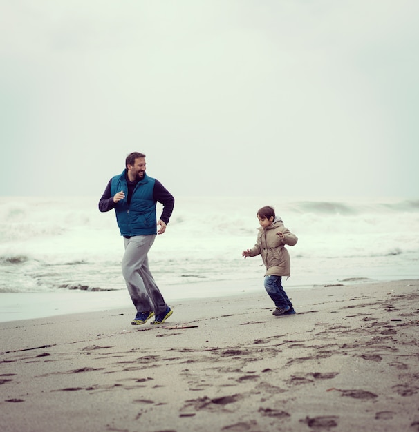 Pai e filho se divertindo na praia de inverno Foto Premium