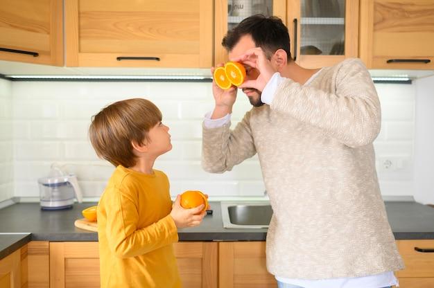 Pai e filho segurando metades de laranjas Foto gratuita