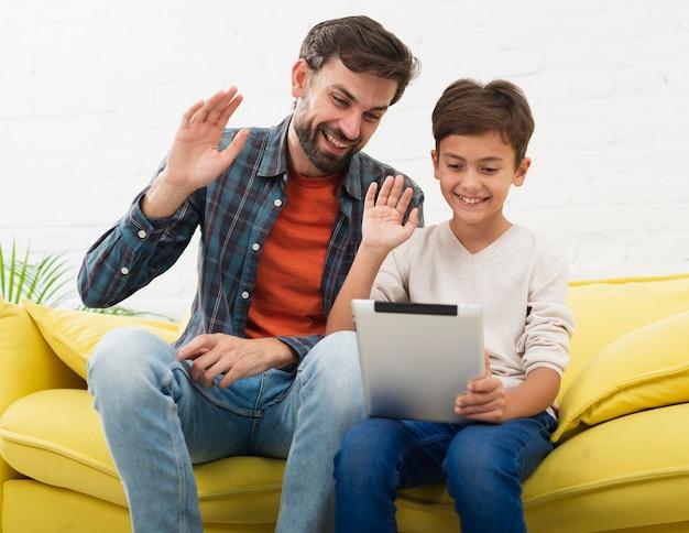 Pai e filho segurando um tablet e saudando Foto gratuita