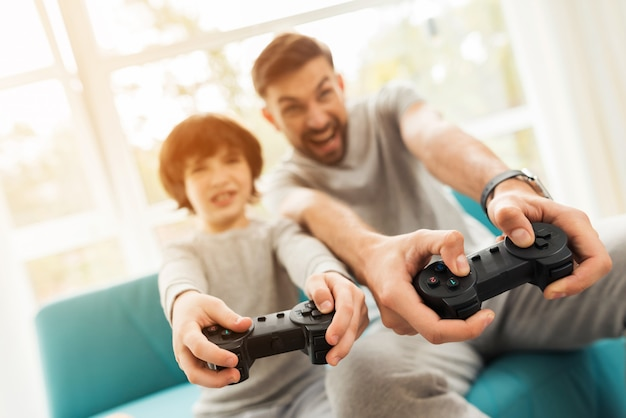 Pai e filho sentado e jogando no console. Foto Premium