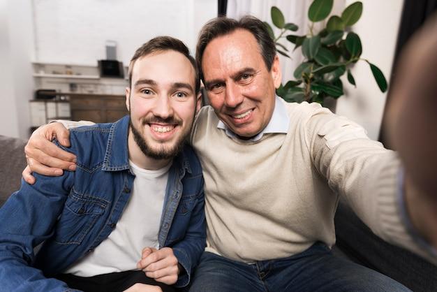 Pai e filho tomando uma selfie a sorrir Foto gratuita