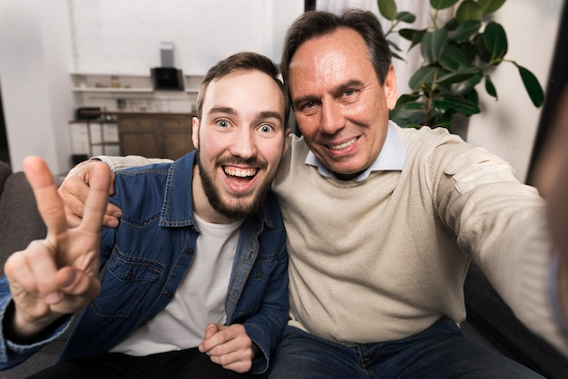 Pai e filho tomando uma selfie engraçada Foto gratuita