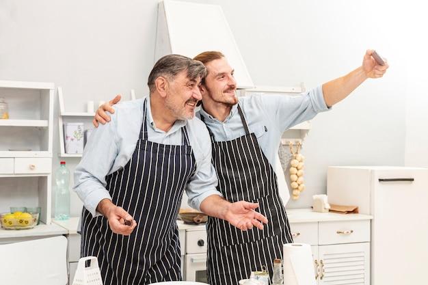 Pai e filho tomando uma selfie na cozinha Foto gratuita