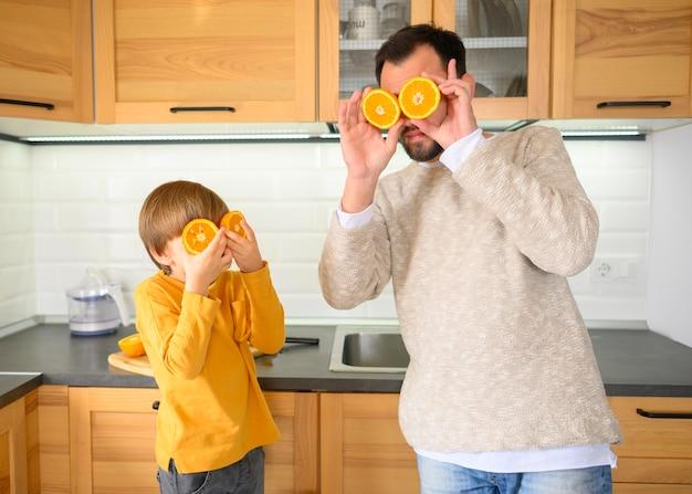 Pai e filho usando metades de laranjas para cobrir os olhos Foto gratuita