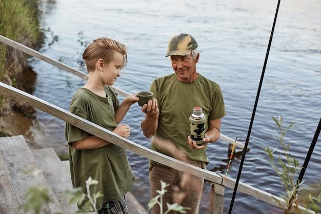 Pai e filho vão pescar, beber chá de garrafa térmica em pé escadas de madeira que levam à água, a família descansando na natureza linda, desfrutando de estar ao ar livre ao ar livre. Foto Premium