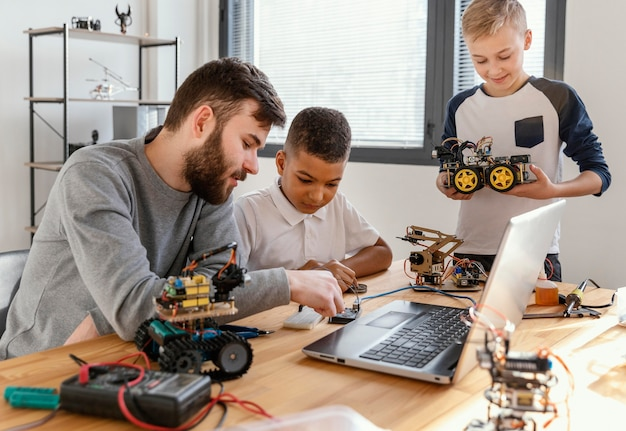 Pai e filhos fazendo robô Foto gratuita