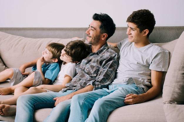 Pai e filhos no sofá no dia dos pais Foto gratuita