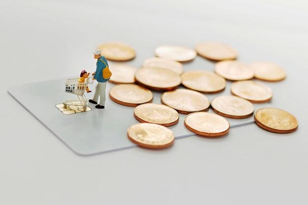 Pai e filhos vão às compras com carrinho no cartão de crédito e moedas. Foto Premium