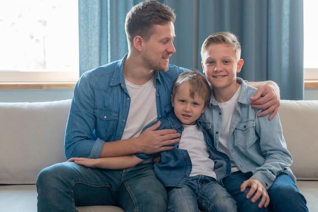 Pai e irmãos bonitos, sentado no sofá Foto gratuita