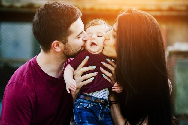 Pai e mãe beijando um bebê nas bochechas Foto gratuita